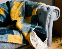 100% British made heritage quilt with a contemporary twist. This quilt is stitched in a traditional strip design made from; sunshine yellow, grey and navy blue tartan Harris Tweed, trimmed with retro Hedgerow by renowned designer Angie Lewin and backed in a smoky grey velvet.