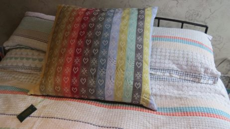 Folklore Fabric metered lengths in a Ecru colourway stitched into a cushion.