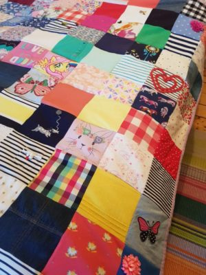 Memory quilt stitched from daughter' clothes.