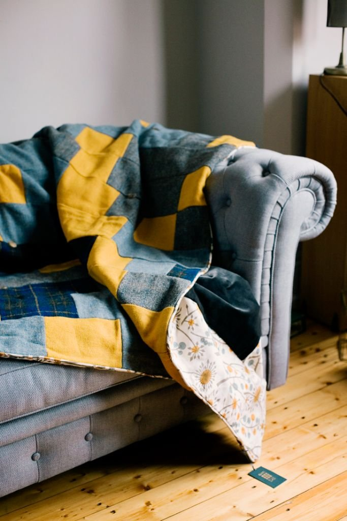 This quilt is stitched in a traditional strip design made from; sunshine yellow, grey and navy blue tartan Harris Tweed, trimmed with retro Hedgerow by renowned designer Angie Lewin and backed in a smoky grey velvet.